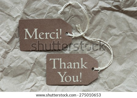 Two Brown Labels Or Tags With White Ribbon On Crumpled Paper Background. French Text Merci Means Thank You And English Thank You Vintage Or Retro Style - stock photo