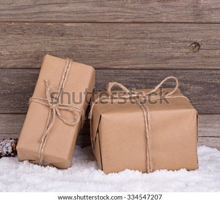 Two brown packages on snow with wood background - stock photo
