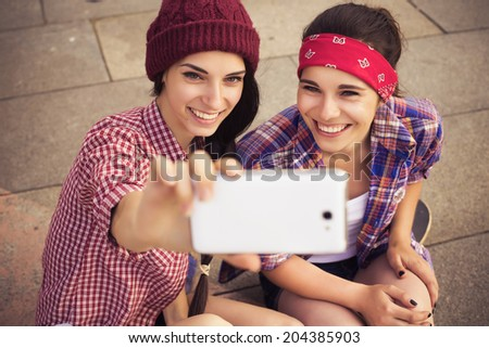 Two Brunette teenage girls friends in hipster outfit (jeans shorts, gumshoes, plaid shirt, hat) with a skateboard at the park outdoors make selfie on a phone.  - stock photo