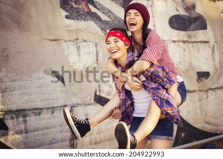 Two Brunette teenage girls friends in hipster outfit (jeans shorts, gumshoes, plaid shirt, hat) with a skateboard at the park outdoors. Copy space - stock photo