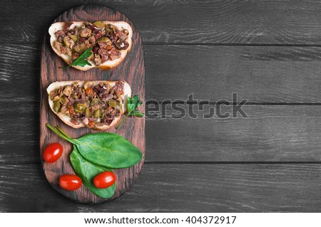 Two bruschetta sandwich with capers, kalamata olives and fresh herbs, cherry tomatoes red, spinach leaves, parsley, served on the Board at a gray wooden surface, top view - stock photo