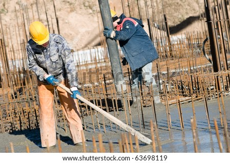 two builder workers during concrete works at construction site. Leveling and pouring - stock photo