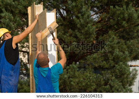 Two builders erecting insulated wooden wall panels on a new house carefully aligning them for installation - stock photo