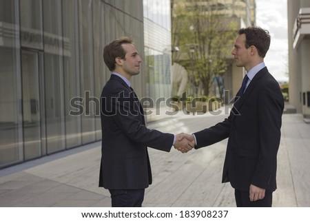 two buisnessman shaking hands outside, partnership, greetings - stock photo
