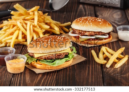 two burgers with grilled meat with french fries on craft paper on wooden surface in kitchen. Fast food template. real photo - stock photo