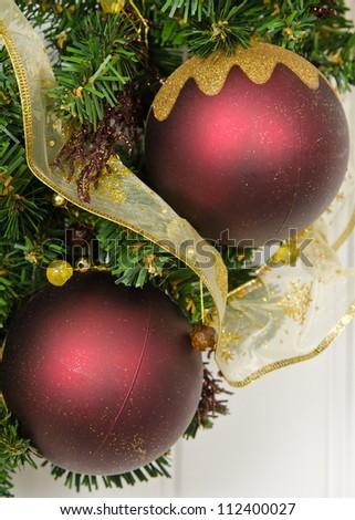 Two burgundy Christmas balls on a wreath - stock photo