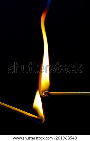 Two burning matches burn against a black background. The orange flames envelop the black match heads. The picture is very serene and useful for a great array of illustrations. soft focus - stock photo