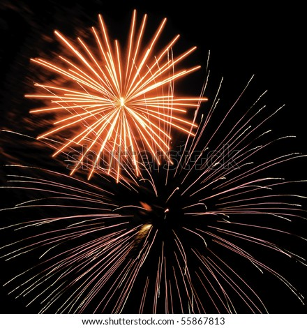 Two bursts of fireworks, the larger with silvery and pink streaks, the other yellow-white with reddish smoke - stock photo