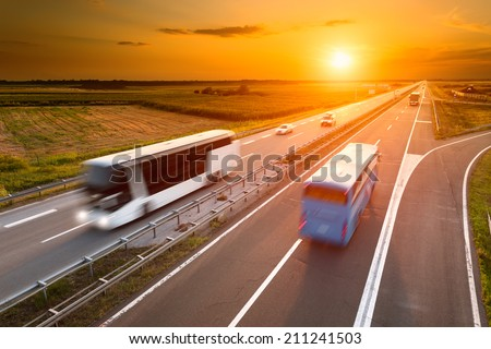 Two buses on highway in motion blur at sunset - stock photo