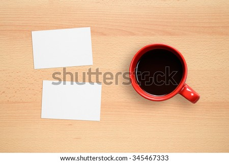 Two business cards and coffee cup on office desk - stock photo