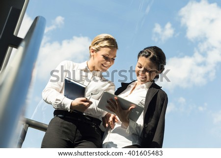Two business colleagues discussing work related matters on an office building hallway - stock photo