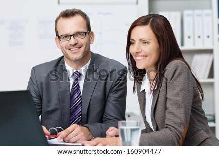 Two business colleagues having a discussion seated together at a desk in front of a laptop computer smiling happily - stock photo