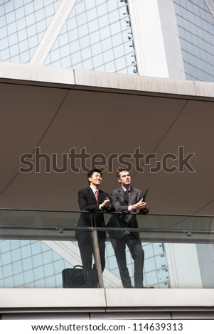 Two Business Colleagues Having Discussion Outside Office Building - stock photo