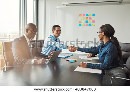 Two business colleagues shaking hands across the table in congratulations during a multiracial business meeting at a conference table in the office - stock photo