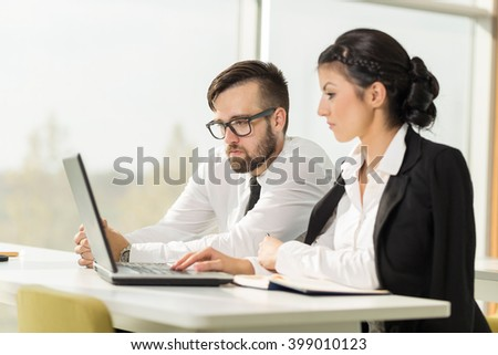 Two business colleagues working on a laptop computer in an office - stock photo