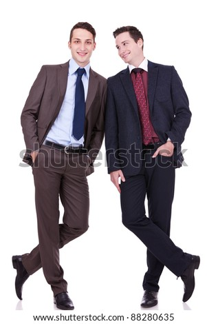 two business friends standing shoulder to shoulder, one looking at the other, over white background - stock photo