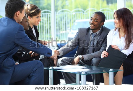 Two business man shaking hands with his team in office - stock photo