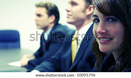 two business men look confidently woman looks towards the camera - stock photo