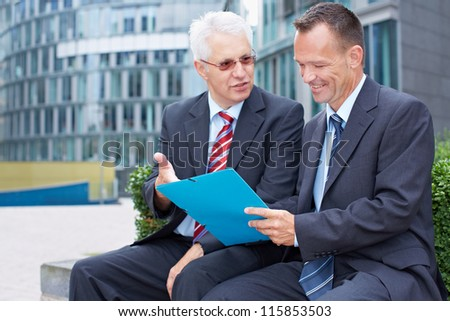 Two business men partner talking about a file - stock photo