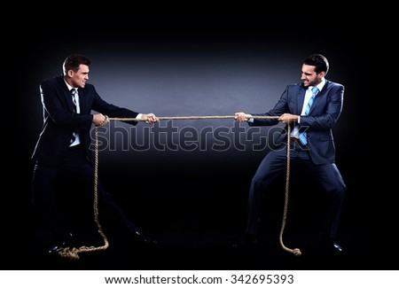 Two business men pulling rope in a competition, isolated on white background - stock photo