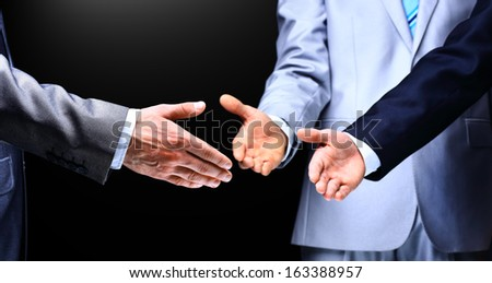 Two business men shaking hands to their leader, close up - stock photo