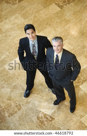 Two business men stand on a marble floor with hands in their pockets. They are looking up towards the camera. Vertical shot. - stock photo