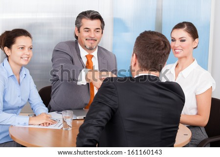 Two Business Partner Shaking Hands In Front Of Colleagues - stock photo