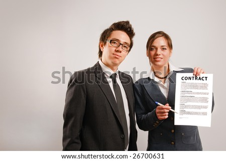 Two business partners holding a printed contract - stock photo