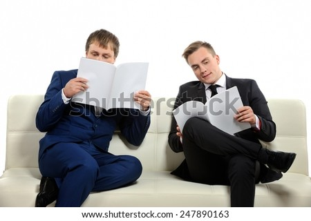 Two business people analyse current business situation and plans for the future. There may be knowledge-sharing context as well.  Copy space on the magazines or above is for your text.  - stock photo