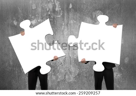 Two business people assembling blank white jigsaw puzzles with concrete wall background - stock photo