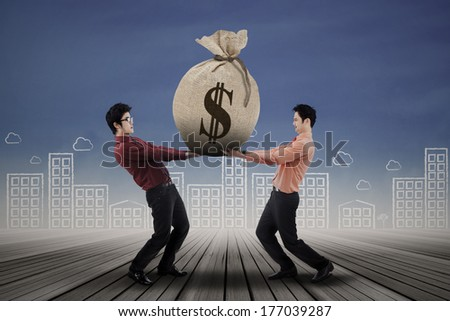 Two business people carrying a money bag with US dollar sign - stock photo