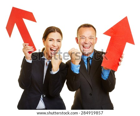 Two business people cheering with red arrows pointing up - stock photo