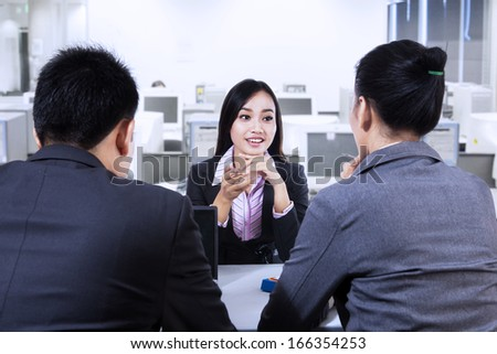 Two business people having job interview with young woman - stock photo