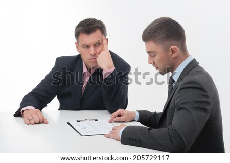 Two business people in elegant suits, chief looking suspicious at employee, holding clipboard with papers isolated on white background - stock photo