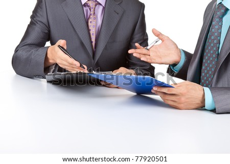 Two business people in elegant suits sitting at desk working in team together and discussing the problem holding clipboard, folder with papers, document, business plan. Isolated over white background. - stock photo