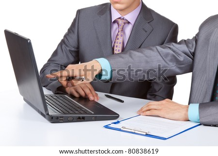 Two business people in elegant suits sitting at desk working in team together, discussing the problem, point finger working on laptop, clipboard with papers, document, Isolated over white background - stock photo