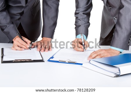 Two business people in elegant suits standing at desk working in team together, working with documents sign up contract, clipboard, folder with papers, business plan. Isolated over white background. - stock photo