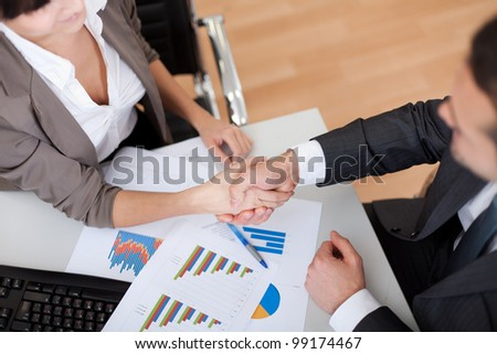 Two business people in the office at the meeting. Close-up on handshake - stock photo