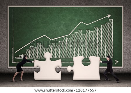 Two business people joining missing puzzle together on profit bar chart background - stock photo