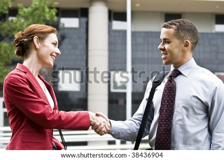 Two business people outside a downtown building greeting each other with a handshake. - stock photo