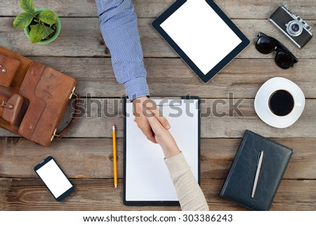 Two Business people shaking hands indoors over a table - stock photo