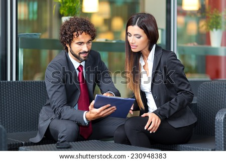 Two business people sitting outdoor - stock photo