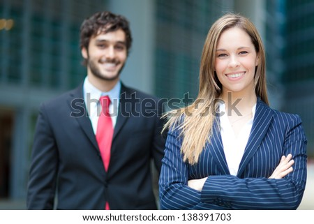 Two business people smiling outdoor in a modern city - stock photo