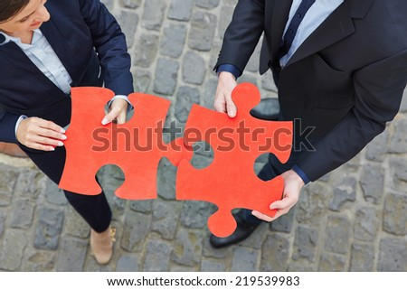 Two business people solving big red jigsaw puzzle pieces together - stock photo