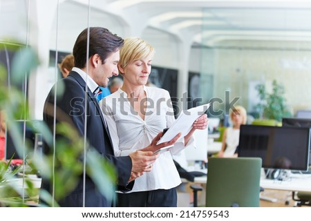 Two business people talking about a contract in office - stock photo