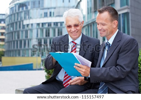 Two business people talking about a contract outside - stock photo