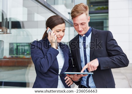 Two business people using smartphone and tablet computer in the vcity - stock photo