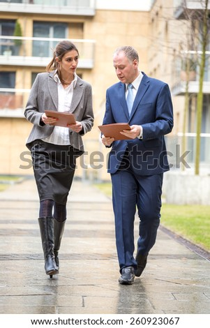 Two business people walking and discussing outside the office - stock photo