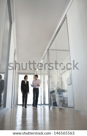 Two business people walking while talking in hallway - stock photo
