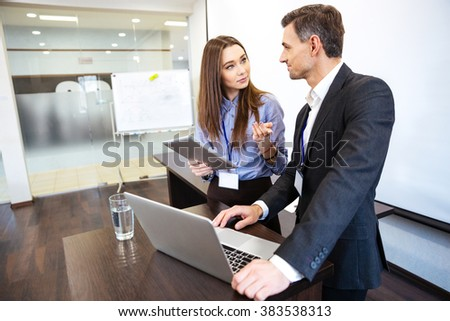 Two business people working together using laptop and tablet in office - stock photo
